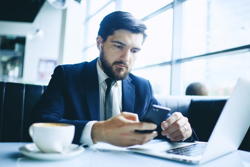 Mann vor Notebook mit Headset ohne Bügel und Smartphone
