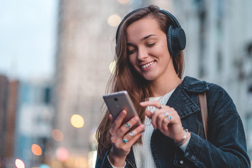 Junge Frau mit Smartphone und Headset